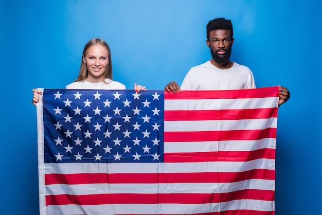 Hombre africano con mujer caucásica sosteniendo la bandera americana aislada en la pared azul