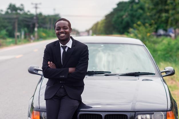 Hombre africano del negocio que se coloca delante de su coche.