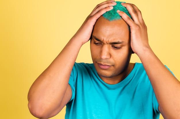 Hombre africano negro en casual en la pared amarilla cansado estresante, tomados de la mano en la cabeza, con dolor de cabeza, dolor