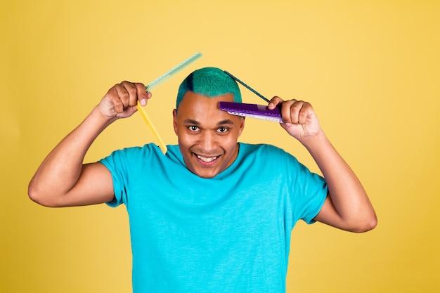 Hombre africano negro en casual en la pared amarilla cepillado de cabello azul brillante, concepto de salón de belleza