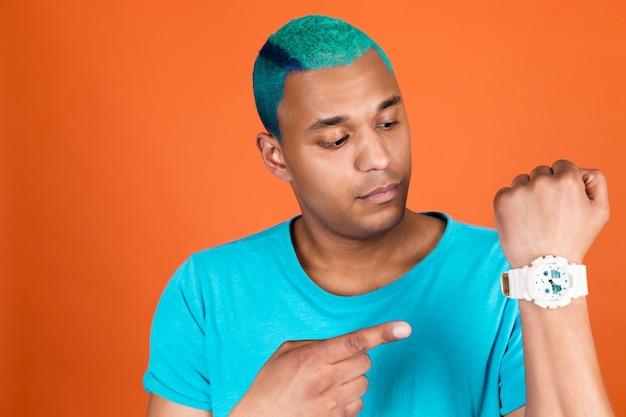 Hombre africano negro en casual en pared naranja cabello azul apuntando en el reloj con cara tranquila, concepto de tiempo de prisa