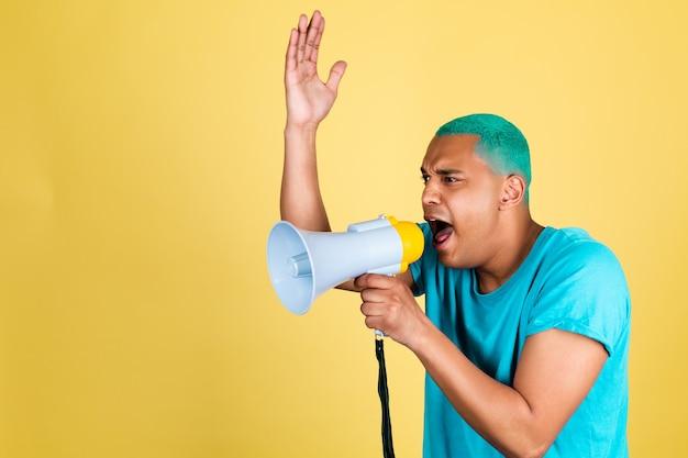 Hombre africano negro en casual sobre pared amarilla cabello azul gritando gritando en megáfono a la izquierda