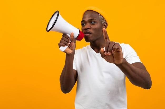 Hombre africano negro habla en megáfono sobre fondo amarillo aislado
