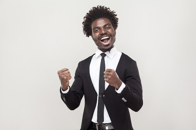 Hombre africano optimista regocijándose de nuevo contrato. tiro del estudio, fondo gris