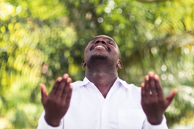 Hombre africano orando por agradecer a dios con la naturaleza verde.