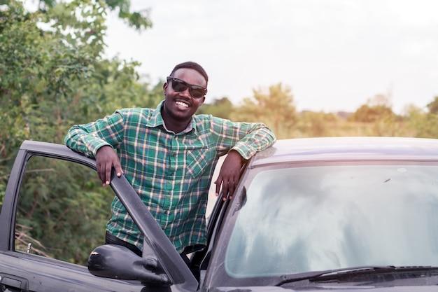 Hombre africano de pie en el camino cerca de la puerta abierta de su coche.