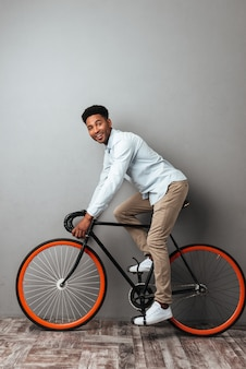 Hombre africano de pie sobre la pared gris con bicicleta.