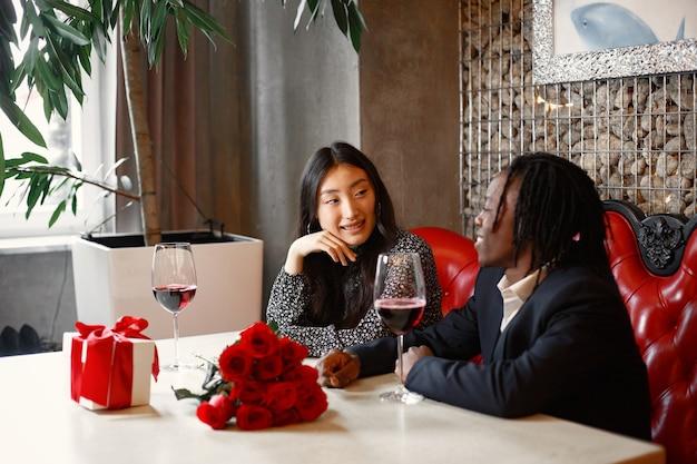 Hombre africano con rastas. vasos con vino tinto. abrazos de una pareja enamorada.