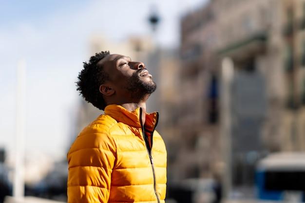 Hombre africano respirando aire fresco al aire libre de pie en la ciudad