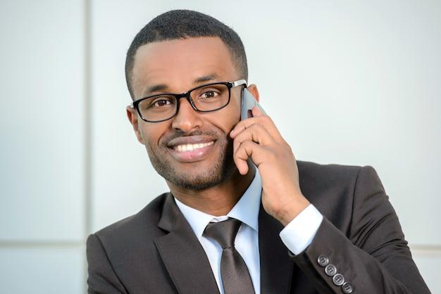 Hombre africano en ropa formal que habla en el teléfono móvil.