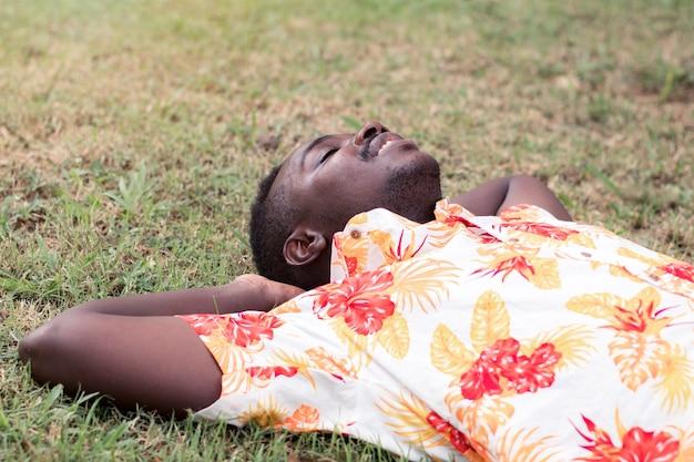 Hombre africano tirado en el suelo en medio de la naturaleza con alegría y comodidad