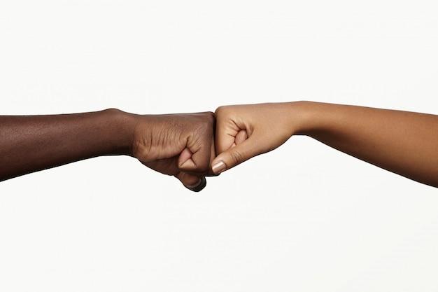 Hombre africano tocando los nudillos con una mujer de piel oscura como signo de acuerdo, asociación y cooperación.
