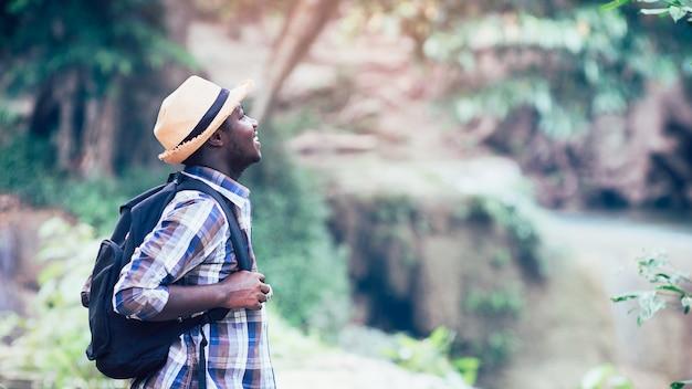 Hombre africano viajero sonríe y relaja en selva
