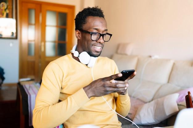 Hombre afro en casa con teléfono inteligente y computadora portátil