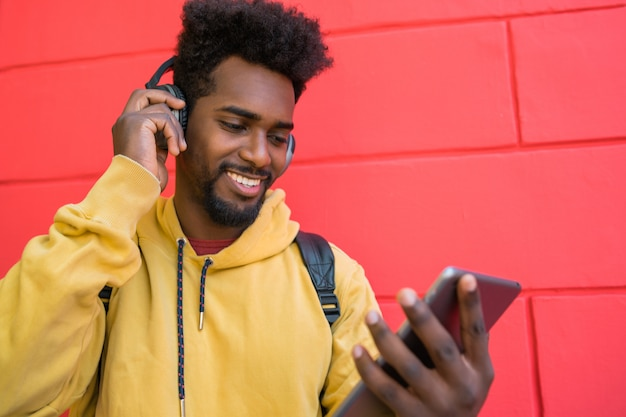 Hombre afro usando su tableta digital con auriculares.