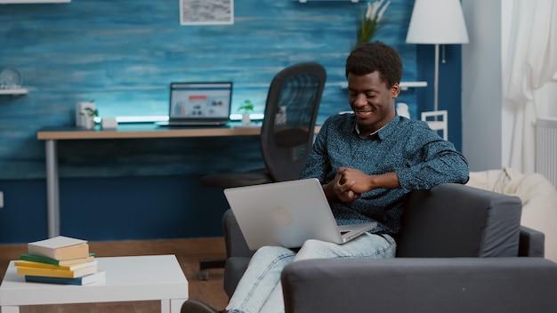 Hombre afroamericano agotado con exceso de trabajo sobrecargado que sufre de privación del sueño, quedándose dormido con la computadora portátil frente a él. retrato de autónomo cansado trabajando desde casa