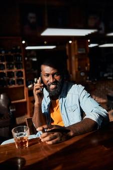 Hombre afroamericano alegre con cigarro hablando por teléfono móvil