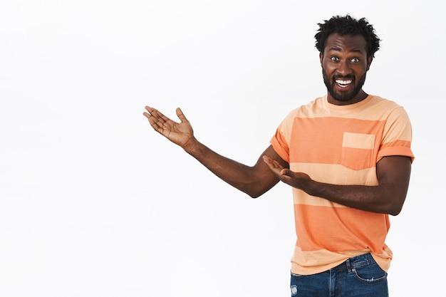 Hombre afroamericano alegre y emocionado con barba y peinado afro presenta algo interesante