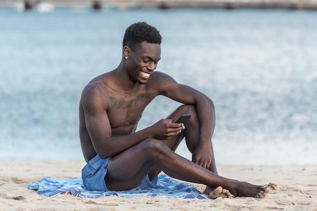 Hombre afroamericano alegre con smartphone en la playa