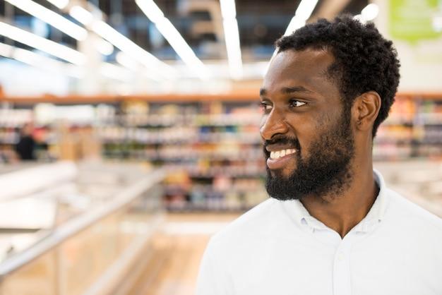 Hombre afroamericano alegre en la tienda de comestibles