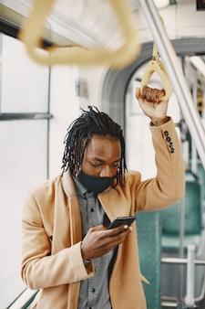 Hombre afroamericano en el autobús de la ciudad. chico con un abrigo marrón. concepto de virus corona.