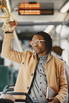Hombre afroamericano en el autobús de la ciudad. chico con un abrigo marrón. hombre con cuaderno.