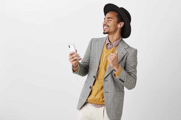 Hombre afroamericano bailando sin preocupaciones escuchando música en auriculares, sonriendo y sosteniendo el teléfono inteligente