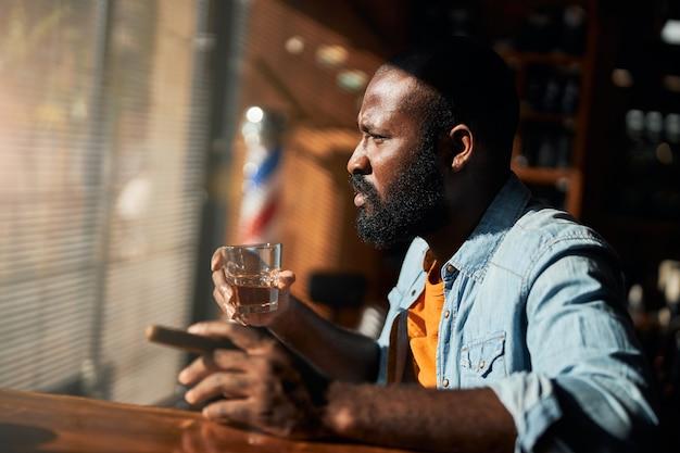 Hombre afroamericano barbudo fumando puros y bebiendo whisky