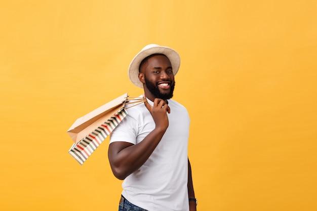 Hombre afroamericano con bolsas de papel de colores aislados sobre fondo amarillo