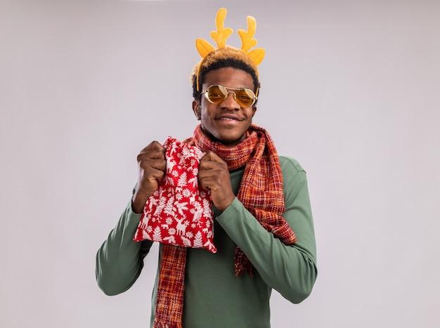 Hombre afroamericano con borde divertido con cuernos de ciervo y bufanda alrededor del cuello sosteniendo una bolsa roja de santa con regalos mirando a cámara feliz y alegre sonriendo de pie sobre fondo blanco