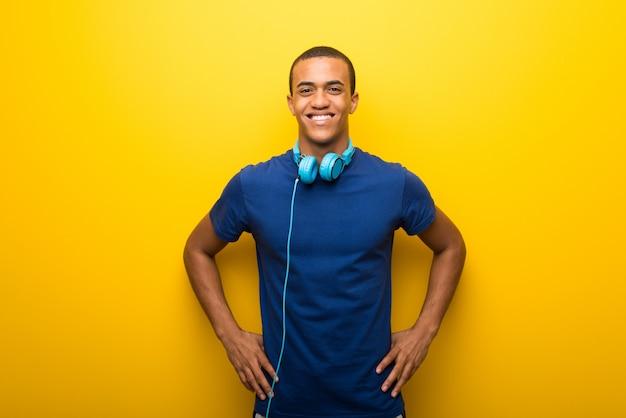 Hombre afroamericano con la camiseta azul en el fondo amarillo que presenta con los brazos en la cadera