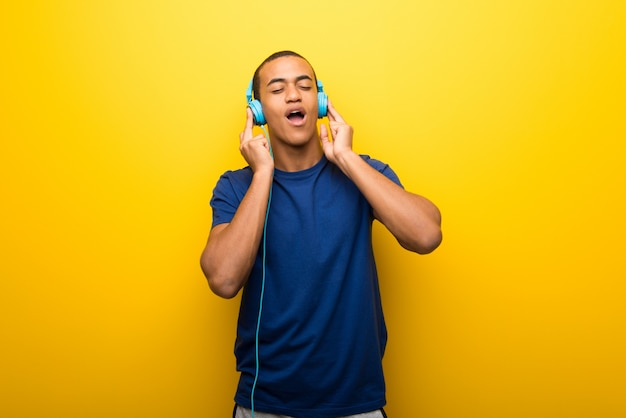 Hombre afroamericano con camiseta azul en la pared amarilla escuchando música con auriculares