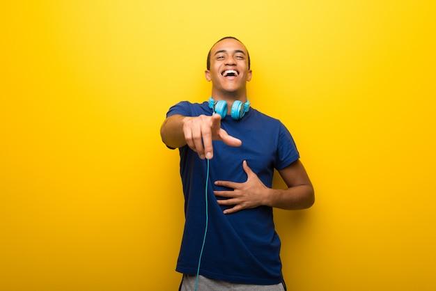 Hombre afroamericano con camiseta azul sobre fondo amarillo apuntando con el dedo