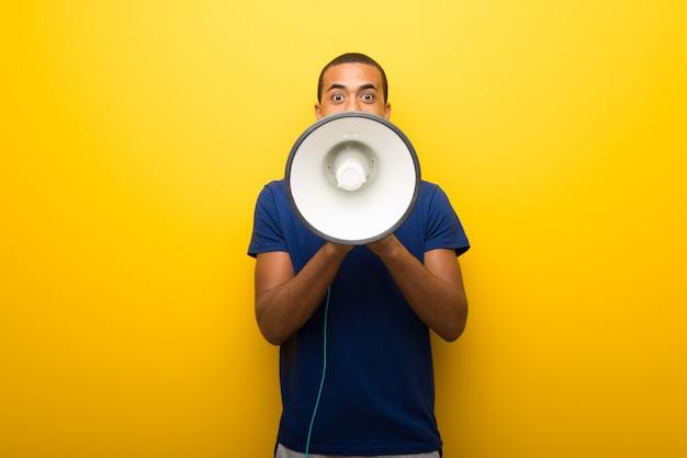 Hombre afroamericano con camiseta azul sobre fondo amarillo gritando a través
