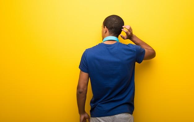 Hombre afroamericano con camiseta azul sobre fondo amarillo