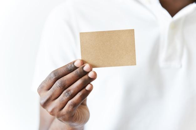 Hombre afroamericano en camiseta blanca con tarjeta de visita