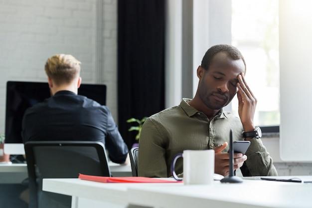 Hombre afroamericano cansado que tiene un dolor de cabeza