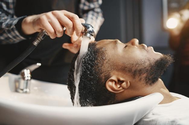 Hombre afroamericano. chico sentado en una silla. lavar pelo.