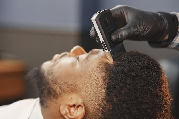 Hombre afroamericano. chico sentado en una silla. el peluquero trabaja con barba.