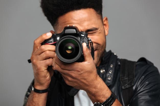 Hombre afroamericano concentrado tomando fotos en cámara digital