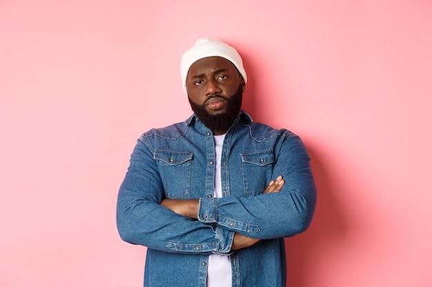 Hombre afroamericano decepcionado en gorro hipster, mirando a la cámara disgustado, brazos cruzados sobre el pecho, de pie sobre fondo rosa