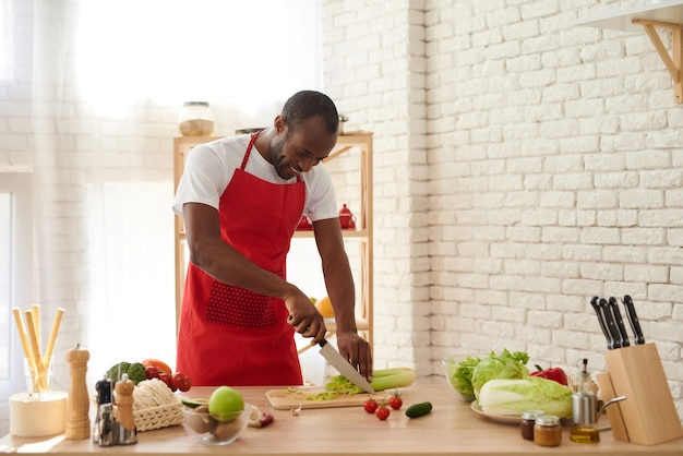 El hombre afroamericano en delantal corta el apio en cocina.