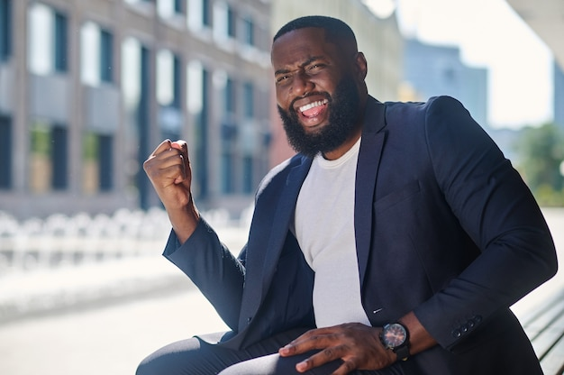 Un hombre afroamericano en un elegante traje sentado en el banco