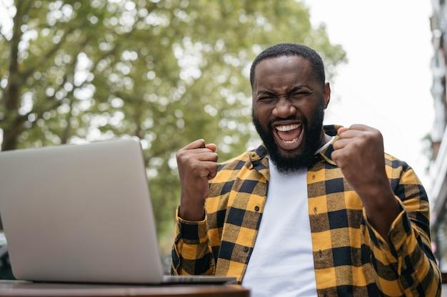 Hombre afroamericano emocional gana éxito de celebración de lotería en línea