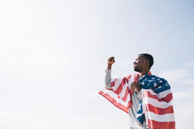 Hombre afroamericano envuelto en la bandera de estados unidos.