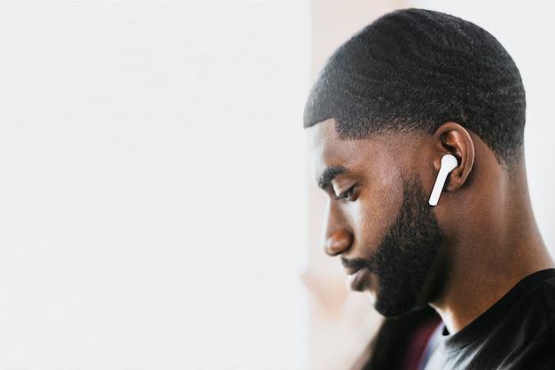 Hombre afroamericano escuchando música con auriculares inalámbricos