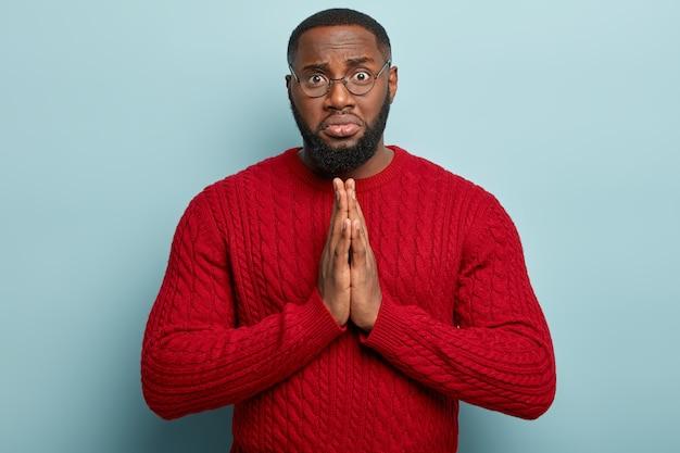 El hombre afroamericano espiritual tranquilo mantiene las palmas juntas, suplica ayuda, tiene una expresión triste y sombría, viste un jersey rojo, aislado sobre una pared azul, pide perdón. concepto de lenguaje corporal