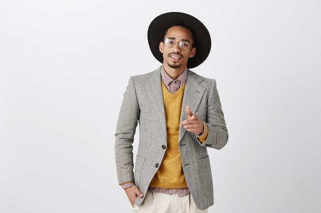 Hombre afroamericano guapo descarado en traje apuntando