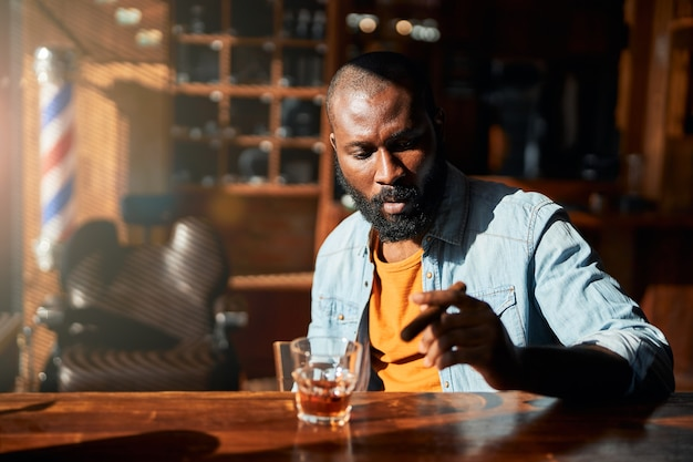 Hombre afroamericano guapo fumando cigarros en el bar de la barbería