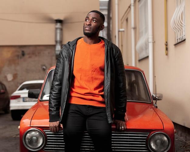 Hombre afroamericano guapo sentado en el coche